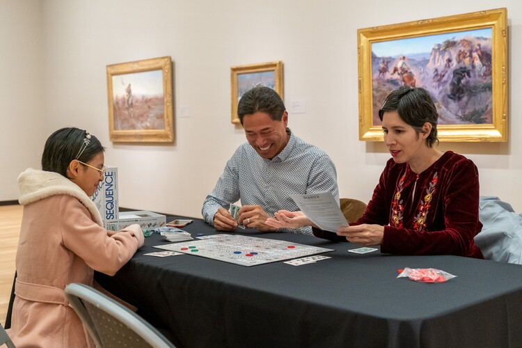 mom, dad, and daughter playing a board game in front of western art