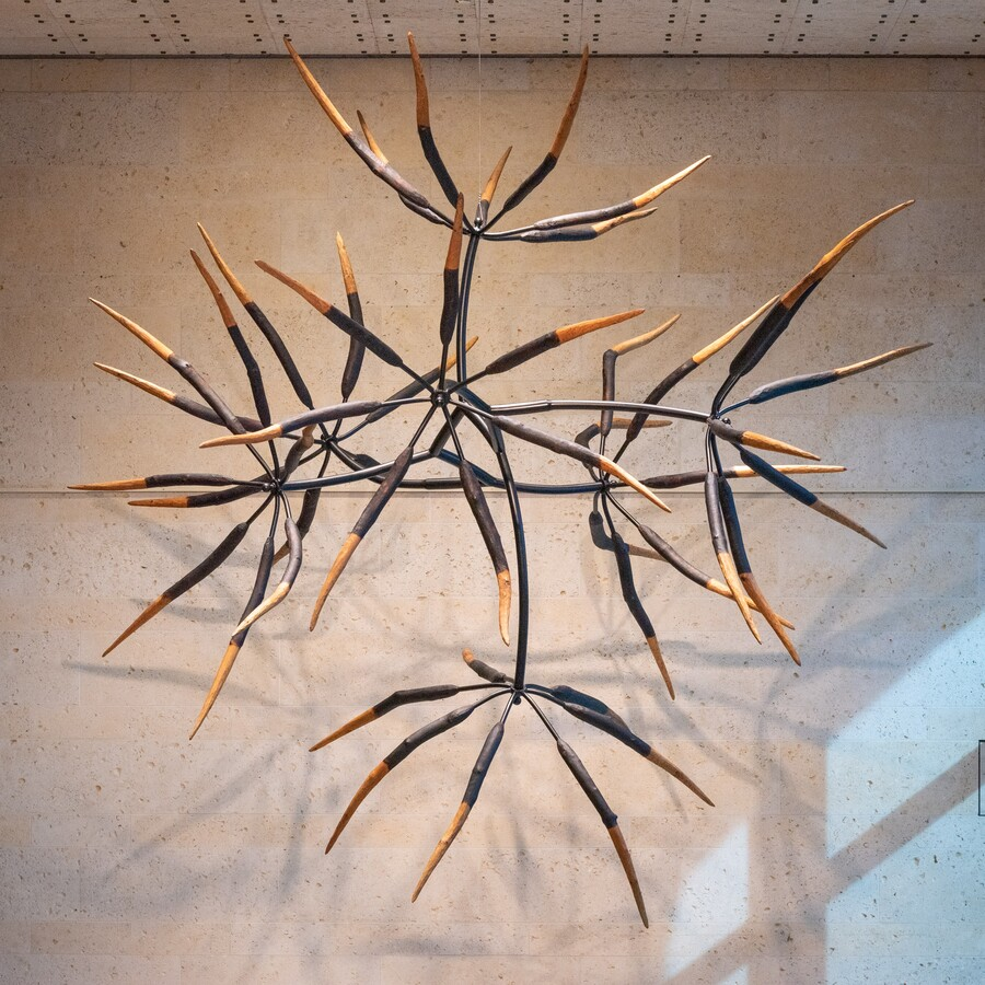 A large direct-carve wooden sculpture with seven parts suspended from the ceiling