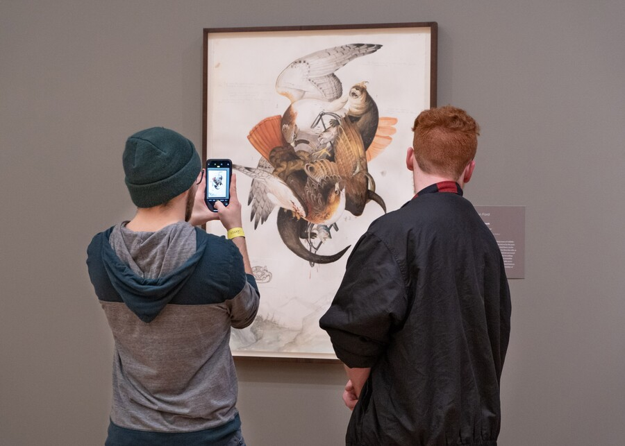 Two people stand in front of an artwork hanging on a wall; the person on the left holds up a smartphone to take a photo