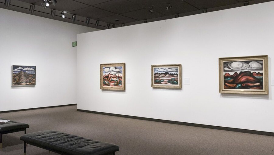 View of gallery with white walls; four framed abstract landscape paintings hang on the walls.