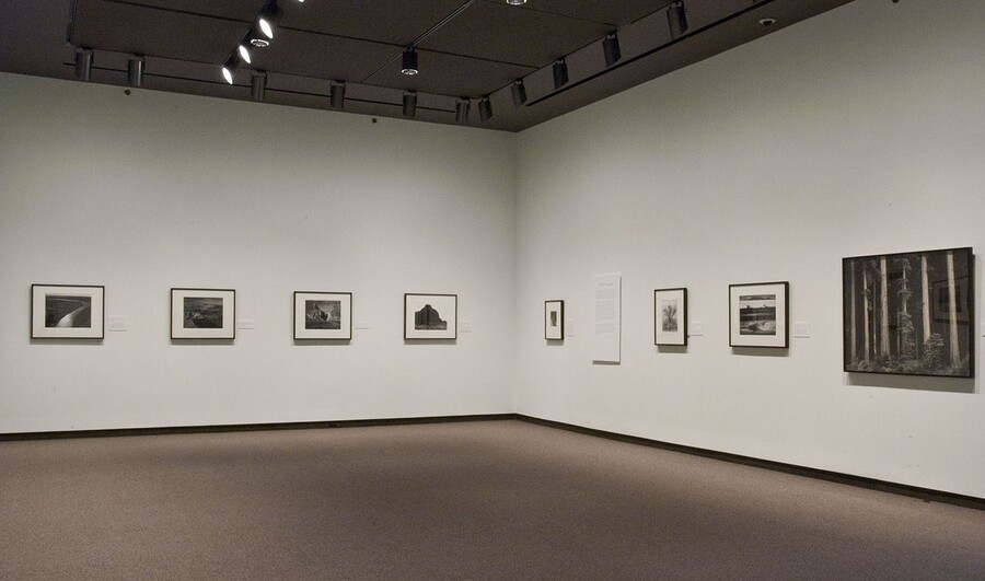 Corner of a gallery showing framed photographs hanging on each wall and one exhibition panel.