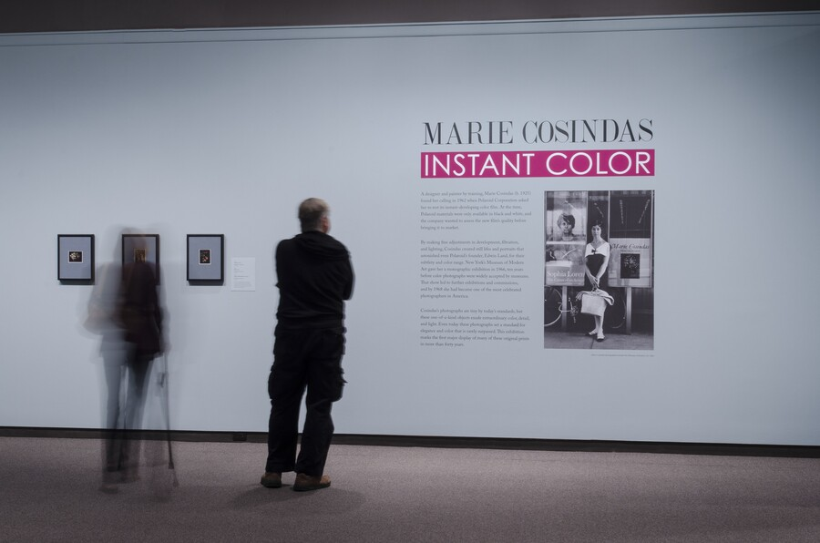 View of exhibition title wall with two people standing in front of it. On the wall are three framed photographs, the exhibition text, and an enlarged black-and-white photo of the artist.