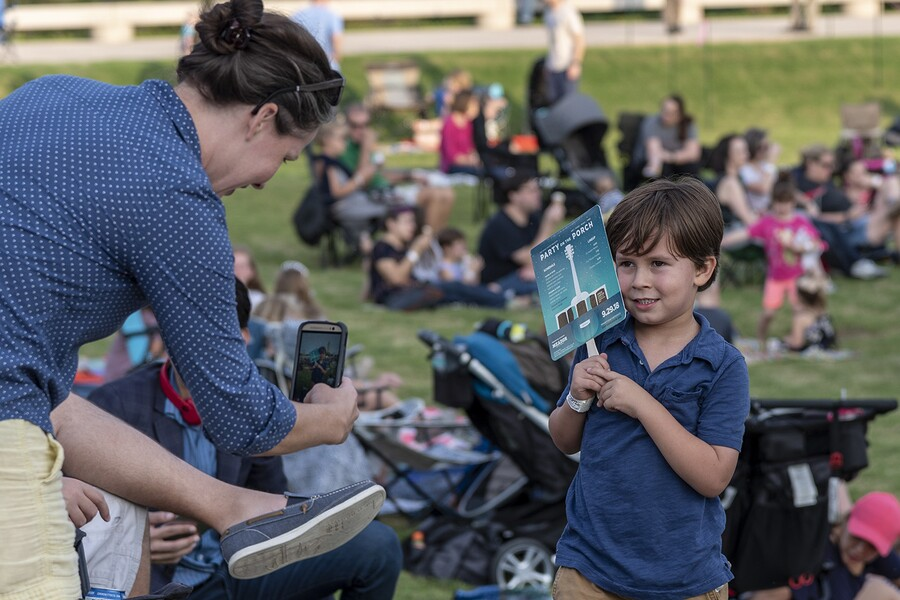 A woman in a blue shirt leans over to take a photo of a little boy holding a cardboard fan; a crowd of people relax on the grass in the background.
