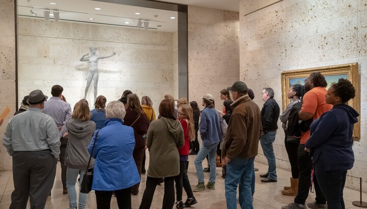 A crowd stands around looking at the sculpture Diana by Augustus Saint-Gaudens