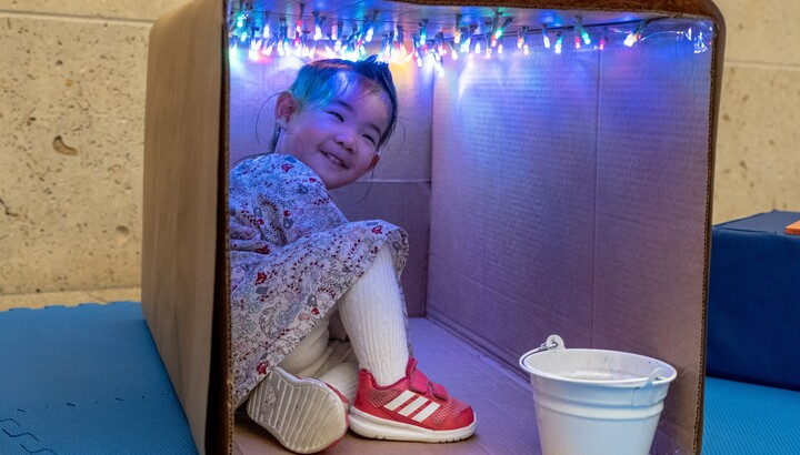 toddler playing in a cardboard box with lights