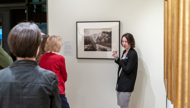 Amon Carter Curator leading a tour in front of a photograph