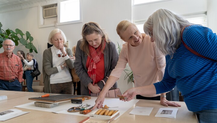 group of women examining art objects on a table