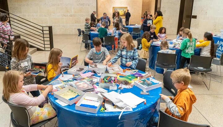 Children work at tables in the Carter atrium