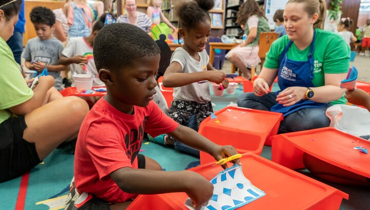 two kids make art with a volunteer