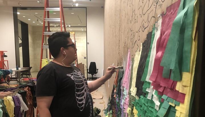 Artist Justin Favela installing Puente Nuevo
