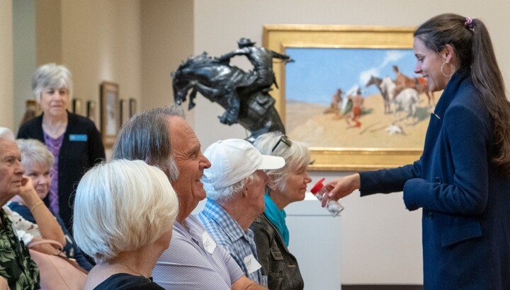 A group smells something held by a staff member in the Carter galleries