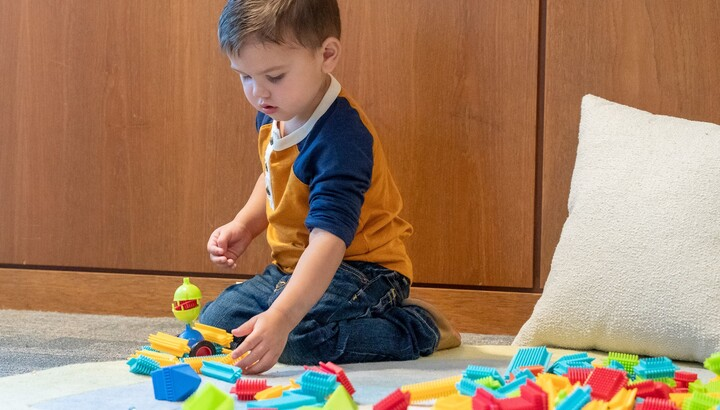 little boy playing with connecting blocks
