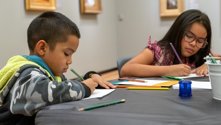 a boy and a girl coloring in an art gallery