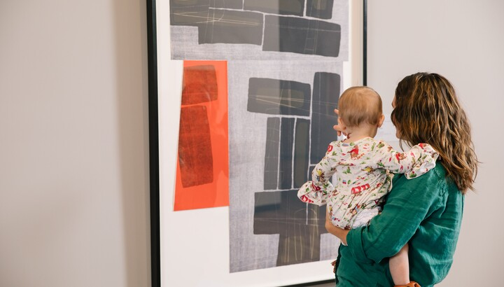 mom and baby looking at a work on paper with black and white and red blocks