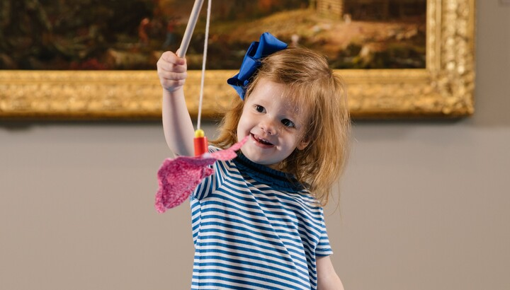 little girl catching a toy fish with a stick in front of a painting