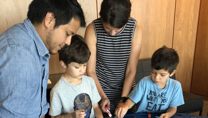 dad, mom, and two boys making art