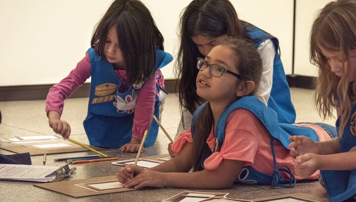 Four girls in Girl Scout daisy uniforms are on the floor of a gallery, three look at a sketching project and one looks up