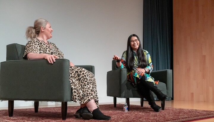 two women sitting in chairs on a stage talking