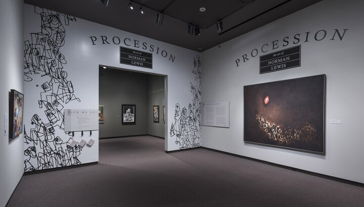 """White title wall for Procession exhibition shows black """"scribbles"""" around an entryway. To the right is a large abstract painting featuring geometric shapes on the bottom of the dark canvas and a red and white circle in the upper left."""