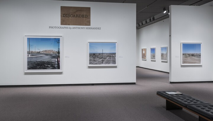 Overview of gallery entrance showing the exhibition title and two artworks to the left of a doorway into the exhibition.