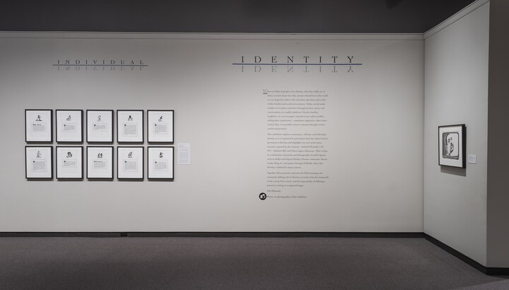 White wall with exhibition text to the right of 10 framed lithographs.