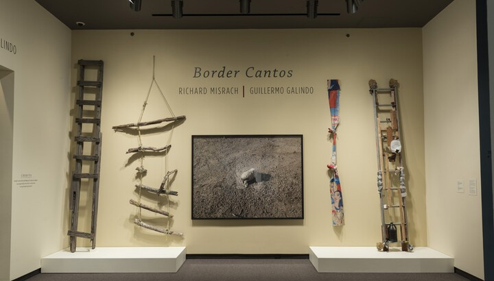 Cream-colored exhibition title wall with photograph of a rock in center. To the left are two crudely-made wooden ladders; on the far right is a ladder covered with detritus, and to its left is a knotted rope made from fabric.