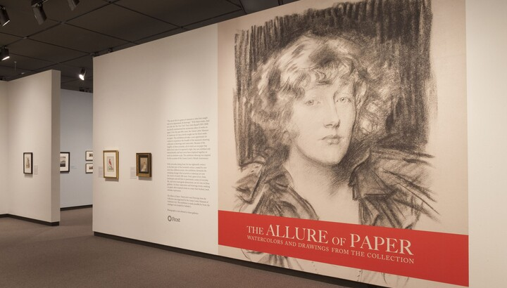 Exhibition title wall showing the title in white on an orange block underneath a large-scale reproduction of a charcoal portrait of a woman.