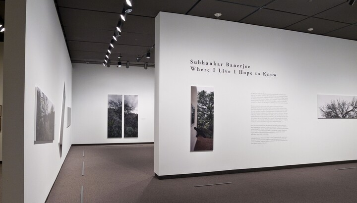 View of exhibition title wall featuring two large-scale photos mounted on a white wall; other photos can be seen on walls within the exhibition.