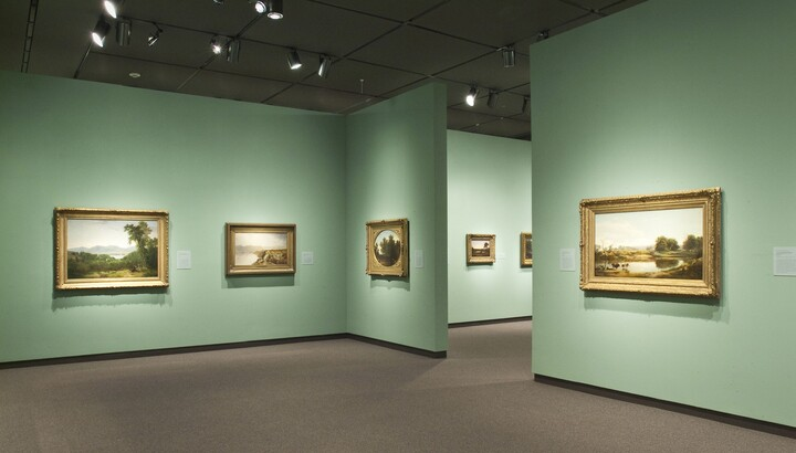 View of a gallery with light green walls. Gold-framed landscape paintings hang on each wall.