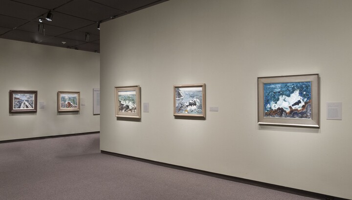 Cream-colored gallery walls with framed paintings hanging on the two visible walls.