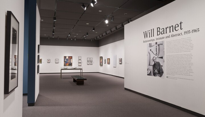 View of gallery; wall on the right has the title graphic and a photo of the artist; the other two visible walls feature framed artwork.