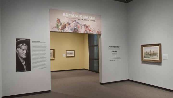 View of gallery title wall and entrance; to the left of the entrance is a large photo of the artist; over the entrance is the title graphic; on the wall to the right is a framed painting. More artwork can be seen through the entrance.