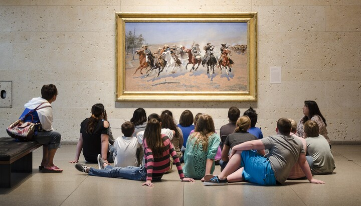 A group of middle-school students sit on the floor in front of a painting of horses and their riders galloping across the plains.