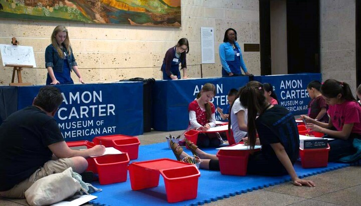 View of the museum's atrium with children and adults sitting on blue mats on the floor working on art projects on red lap desks.