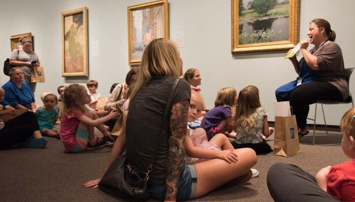 A group of children and adults sit on the floor in a gallery in front of a woman who is seated on a chair and holding up a book for the group to see.