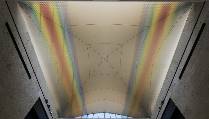 View of the ceiling of the museum's atrium showing the installation of two sections of colored thread stretched from wall to wall creating two rainbows.