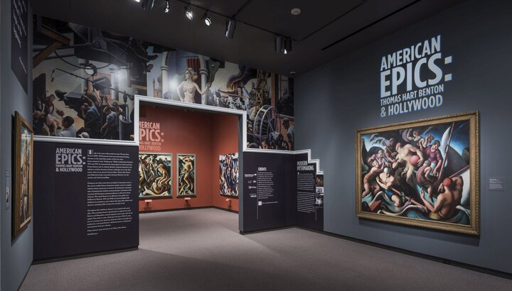 View of exhibition entrance and title wall; to the right is a large framed painting of people on a boat; the entrance wall features a reproduction of artwork showing people in an industrial setting; more framed paintings can be seen through the entrance.