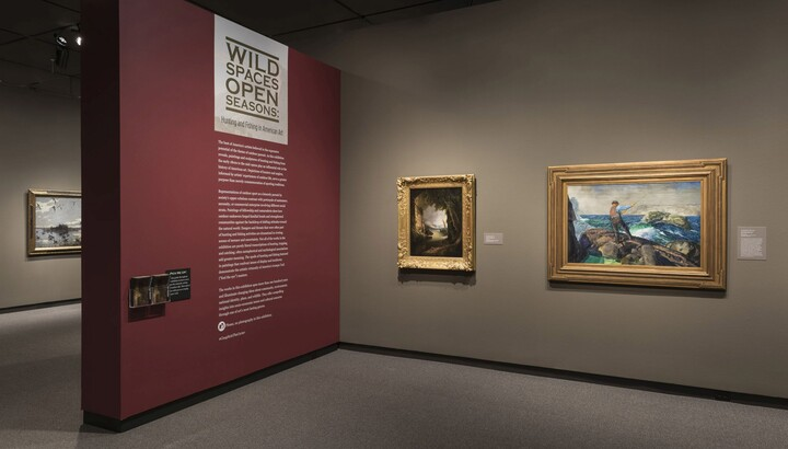 View of exhibition showing a dark red title wall on the left with introductory text; on the right is a tan wall featuring two gold-framed paintings.