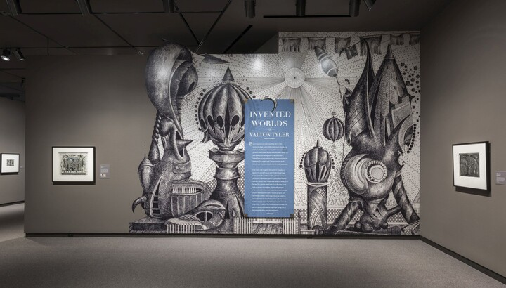 Exhibition title wall featuring an enlarged reproduction of a fantastical black-and-white drawing with introductory text on top of it. To the left and right are framed artworks hanging on taupe walls.