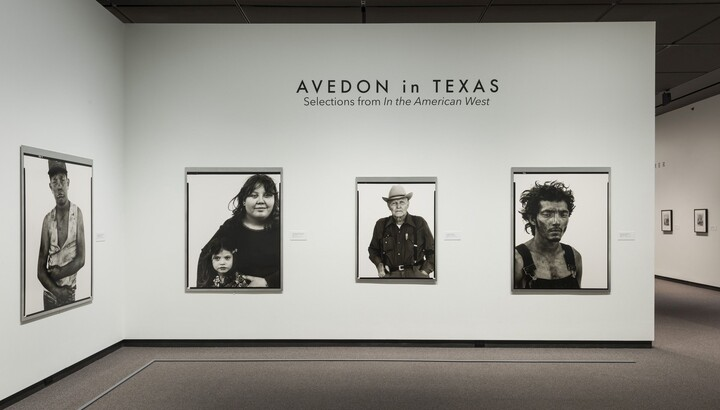 View of exhibition title wall showing three framed black-and-white portraits hanging on a white wall.