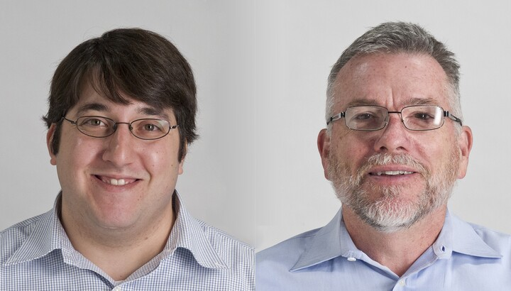 Two men; the one on the left is younger, wears glasses, and has dark hair that hangs over his forehead; the man on the right has short cropped gray hair, a gray beard and mustache, and wears wire-rimmed glasses.