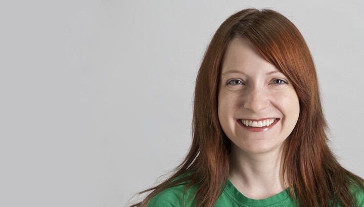 Smiling woman with long red hair wearing a green shirt.