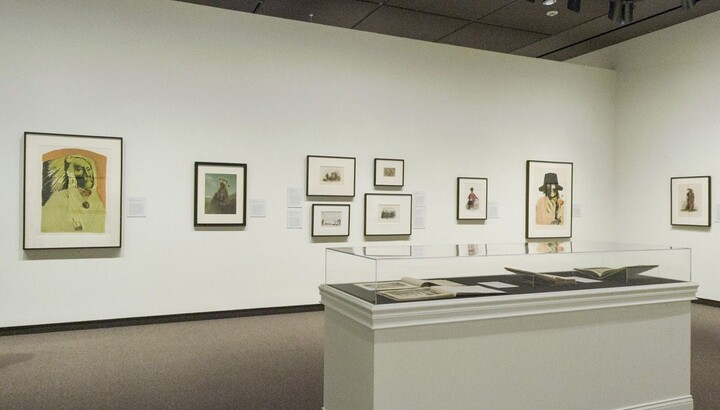 View of a gallery with white walls; framed prints of varying sizes hang on the walls. In the foreground, a glass-covered display case holds several open books.