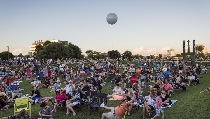 A large crowd of people gather on a grassy lawn in chairs; the Fort Worth skyline is in the background.