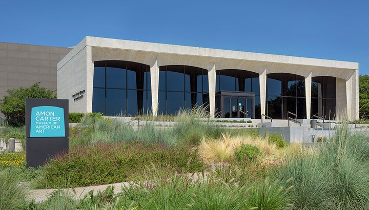 Facade of the Amon Carter Museum of American Art showing landscaping and sign.