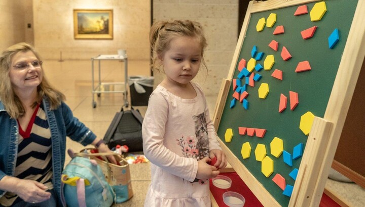 A small child stands at an easel with colored shapes arranged on it as a woman seated on the floor looks on