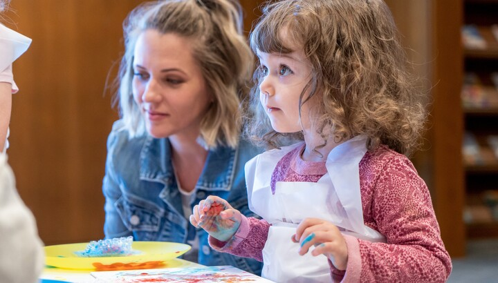 A small child looks up from the painted paper on the table in front of her; her hands are covered in paint