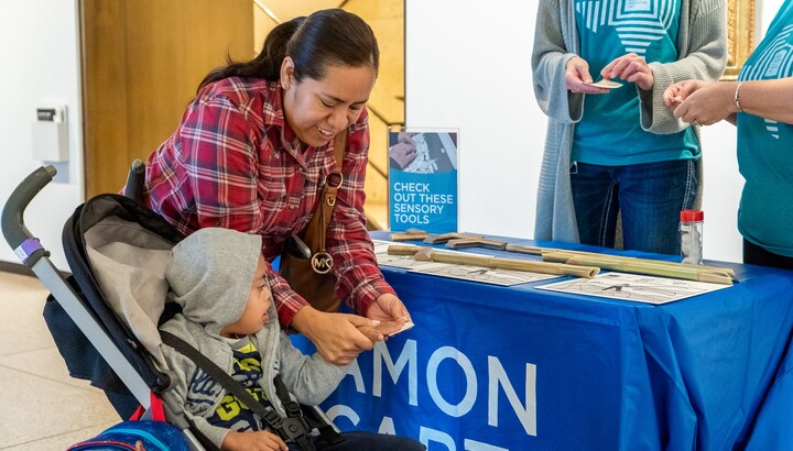 In a gallery, a woman holds material for a young child in a stroller to feel with his hands. Two museum employees in blue shirts stand to the right behind a table with more sensory materials