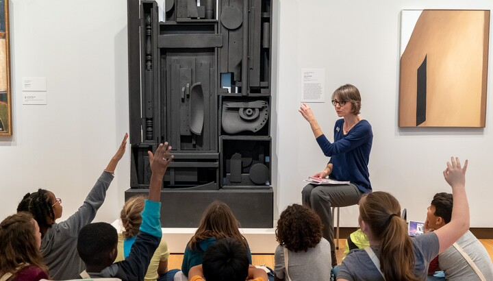 Approximately 10 students sit on a gallery floor, some with their hands up, as a Gallery Teacher talks about a large black sculpture in front of them