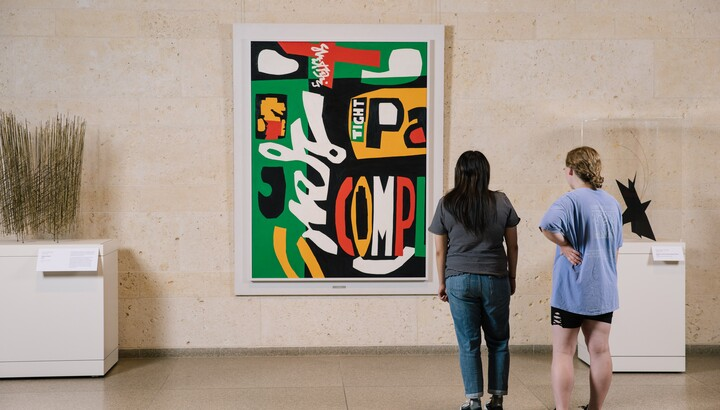 Two people in a gallery stand in front of a large modernist painting by Stuart Davis